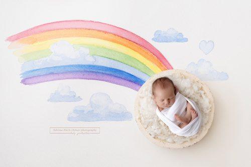 Baby auf Wolke mit handgemalten Regenbogen