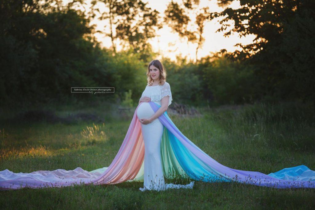 Schwangere mit Regenbogenbaby und Rock in Regenbogenfarben