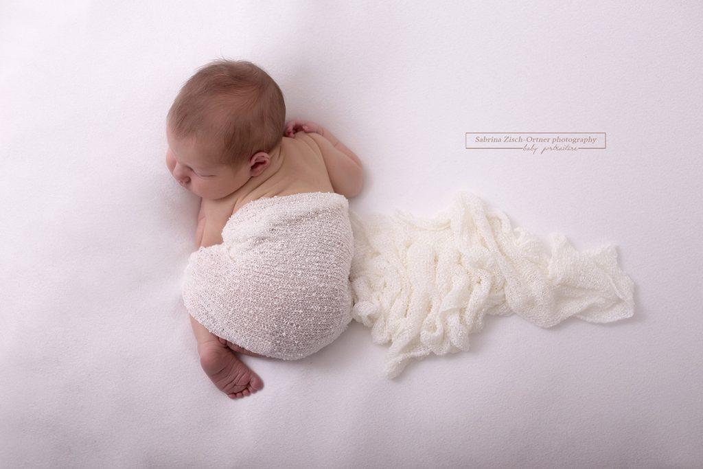 frisch geborene Bursche von oben fotografiert auf Bauch liegend mit weissen Tuch umhuellt