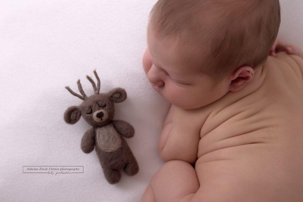 neugeborenes Baby im Winter geboren mit kleinen gefilzten Rentier als Accessoire