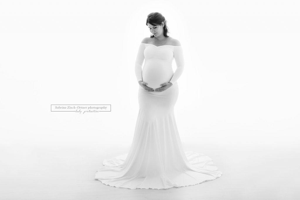 Schwangerschaftsshooting mit weißem langaermeligen Babybauchkleid