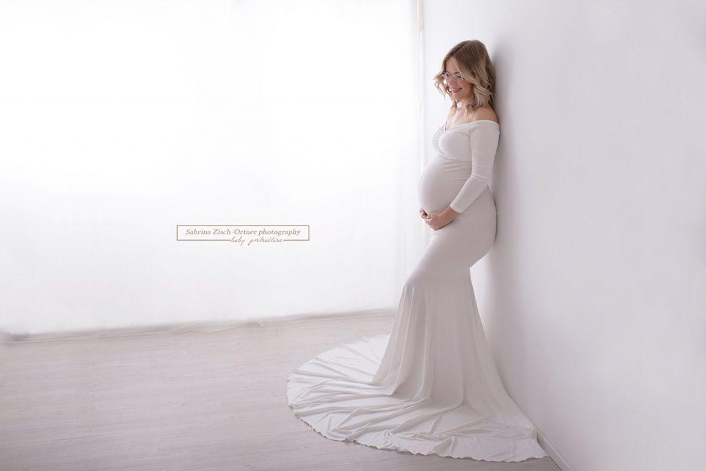 ein bezauberndes Laecheln in einem wundervollen Schwangerschaftskleid