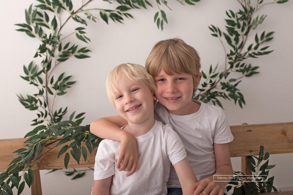 Brueder gemeinsam vor der Kamera in einem Setup aus gruenen Blaettern und selbstgemachter Holzbank