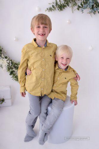 Geschwister lachen aus vollem Herzen bei Weihnachtsshooting in Wien
