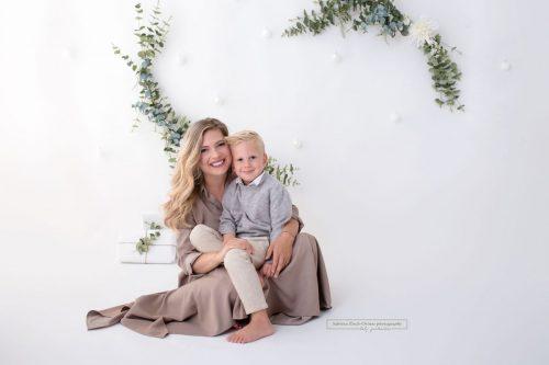 Mama und Sohn kuscheln fuer Foto bei ihren Weihnachtsfotos