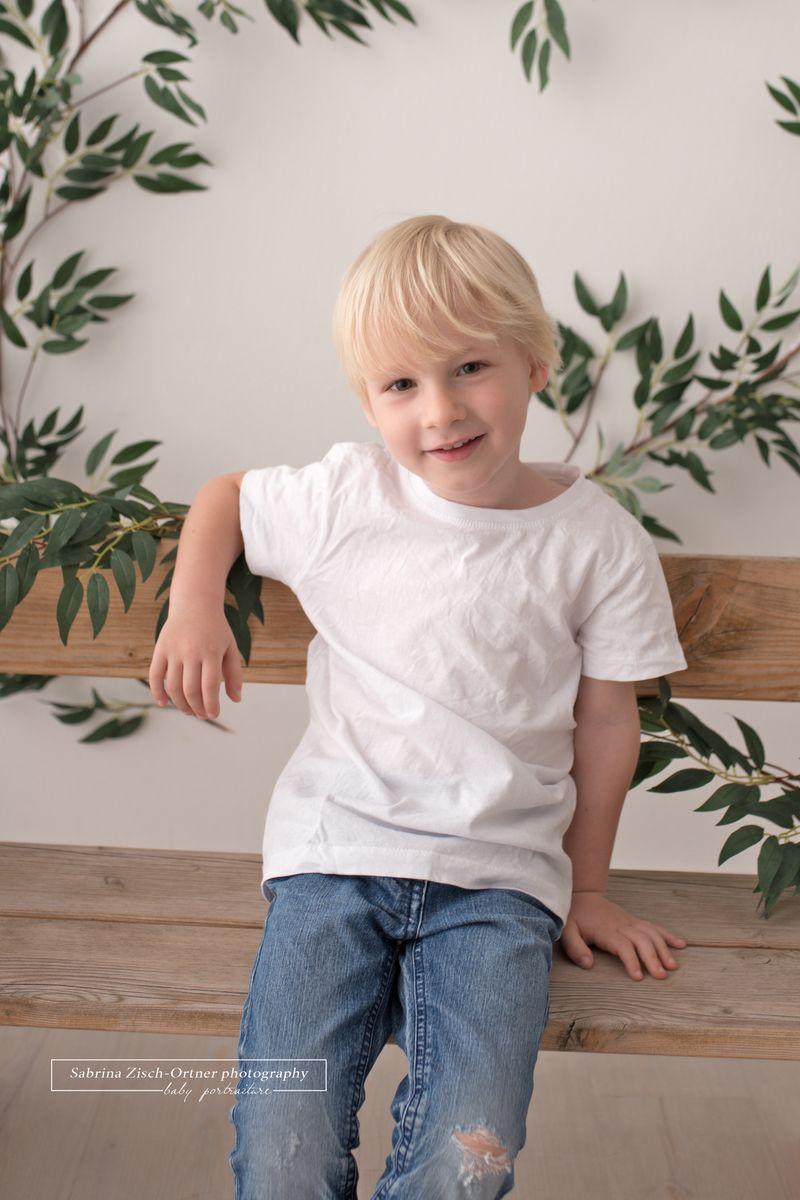 Vier jaehrige lehnt laessig und cool an der Holzbank in blauer Jean und weissem Tshirt fuer sein Fotoshooting