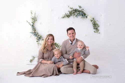 am Boden sitzendes Familienfoto vor weihnachtlichen Hintergrund