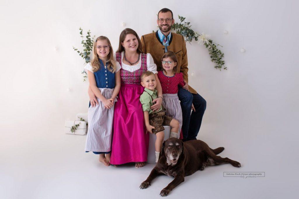 Fuenfkoepfige Familie mit Familienhund beim Fotoshooting