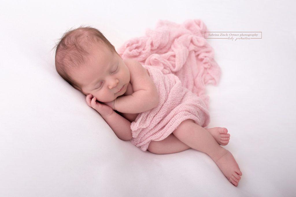 schlafendes Baby bei Fotoshooting mit Rosa Tuch umhuellt