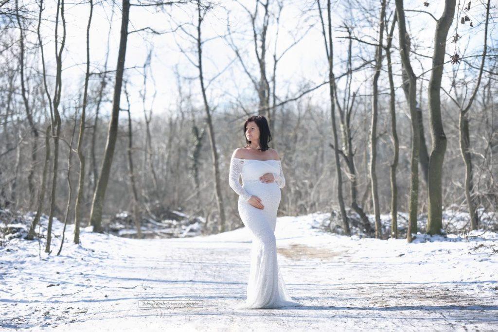 Kleid mit Spitze und langen Ärmeln strahelnd weiß im schneebedeckten Wald für dein Babybauchshooting