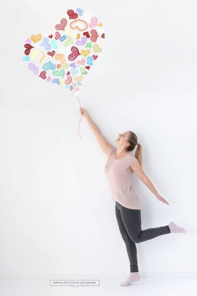 Mama fliegt mit bunten Herzen welche als Luftballon gemacht wurden davon