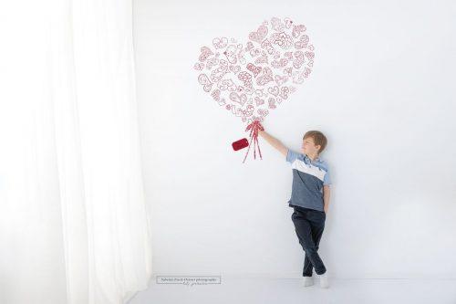 Als Muttertagsgeschenk ein Foto mit Sohn und rotem Herzblumenstrauß