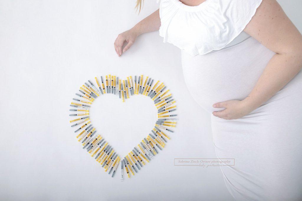 Herz aus Hormon Spritzen der künstlichen Befruchtung IVF neben dem Babybauch der Baldmama
