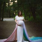 Schwangere im Wald stehend für ihr Fotoshooting mit ihrem Regenbogenbaby im Bauch