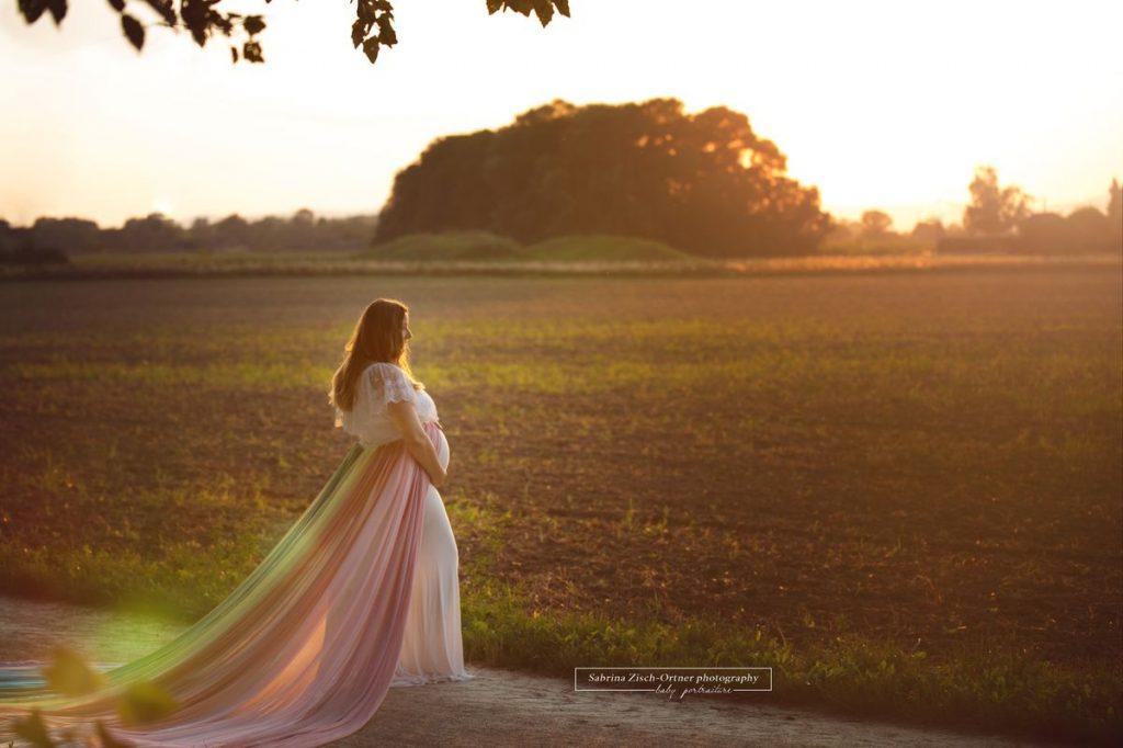 Sonnenuntergang beim Outdoor Babybauchshooting mit Kleid in Regenbogenfarben