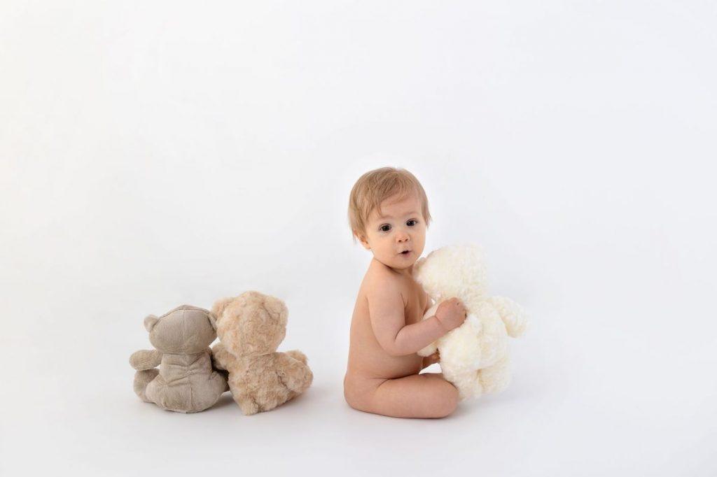 Babyfoto mit Teddybären und überraschendem Gesichtsausdruck des kleinen Mannes