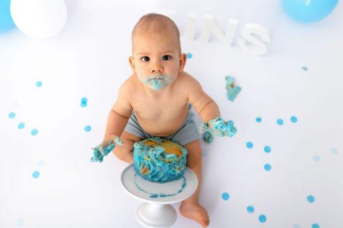zerquetschte Torte und vollgeschmiertes Gesicht des einjährigen Burschen bei seinem Cake Smash Shooting