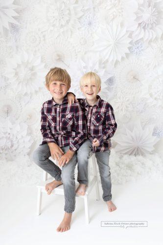 Kinder vor selbstgemachten Schneeflockenwand Hintergrund beim Fotoshooting